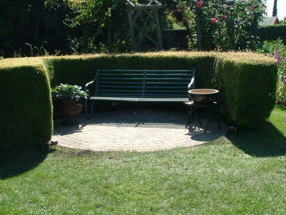 circular brick paving, hedge and garden bench