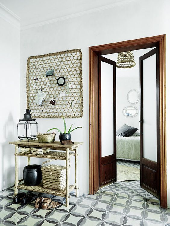 Relaxed hallway with beautiful tiles and bamboo furniture in a relaxed Danish oasis in Palma, Mallorca. Tine K Home.