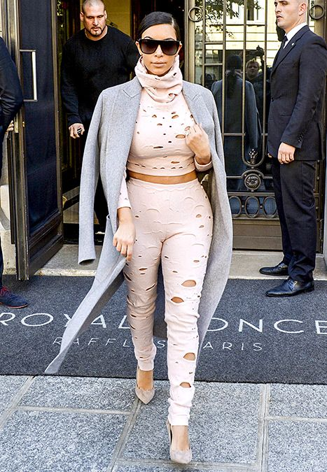 She did it again! Kim Kardashian turned heads during #PFW in a matching crop high-neck top and high-waisted pants, punctured with random holes from head to toe.