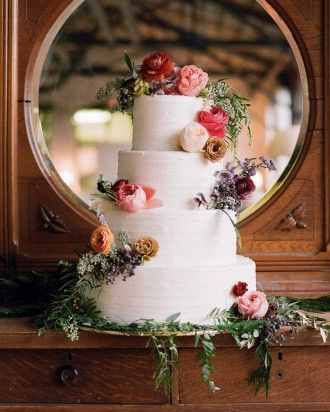 Four-tiered white wedding cake adorned with fresh flowers and greenery