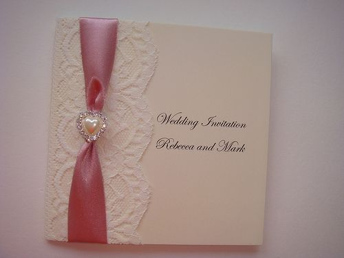 Vintage lace wedding invitation with satin ribbon and a pearl heart
