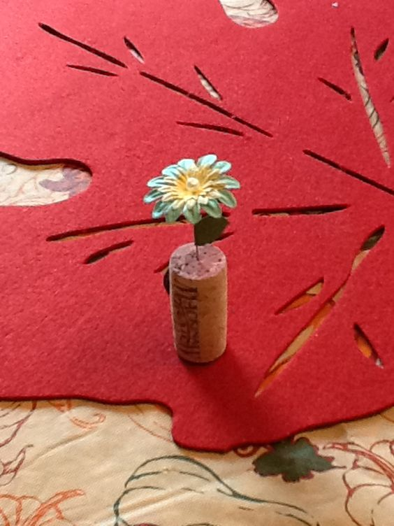 Wine cork flower magnet - use a straight pin, some paper flowers and a leaf then glue a magnet on the back.
