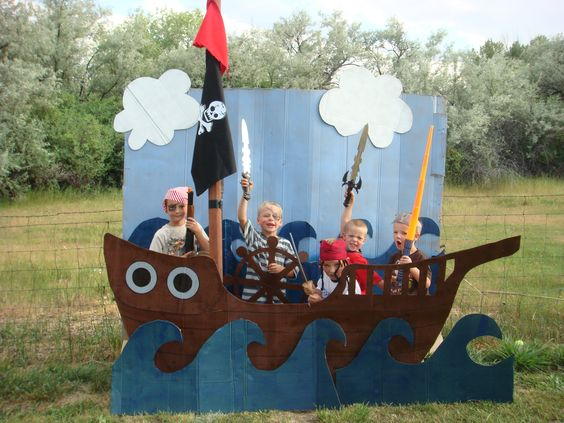 """Kidds Pirate Birthday Party - backdrop. We also dressed them up scars and beards w/ watercolor paints (better to do this *after the squirt gun water fight), did a """"walk the plank"""" balance beam game, and an """"x marks the spot"""" version of pin the tale on the donkey - eye patches worked well for the blind fold - a silver hook from tin foil fished out their funyun chips, and red, black and white streamers lined the trees, same color balloons gathered as a centerpiece for the table and was…"""