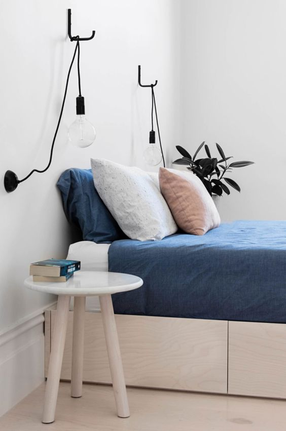 Nice bedroom design in scandinavian style with pendant light bulbs above the bed, small modern bedside table and indoor plants