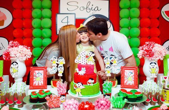 Sofia recebendo um beijo dos pais Aline e Tiago, na festa Magali
