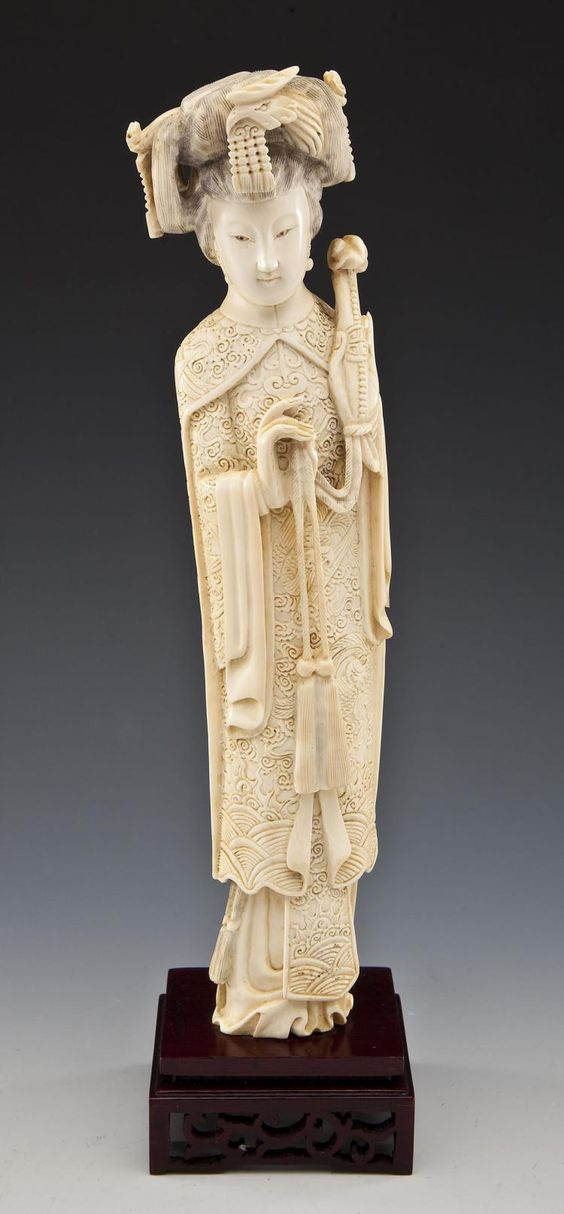 """DESCRIPTION: Carved ivory figure of woman in headdress holding a ruyi (scepter), attached to carved wooden base. MEASUREMENTS: 12"""" tall. CONDITION: Minor wear as expected with handling. IMPORTANT NOTE: Pre-ban and African in origin. From a Pennsylvania estate and acquired during the 1950's to 1980's. Documentation available to the winning bidder upon request. Cannot be shipped out of the United State or to California, New Jersey, or New York. See Auction Terms & Conditions."""