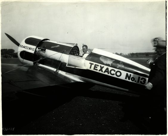"""One-quarter rear left side view, close up, of Frank M. Hawks' Travel Air Model R Mystery Ship """"Texaco No.13"""" (r/n NR1313) on the ground, with Hawks seated in the cockpit; circa 1930. Two other men partially visible blurred at extreme right edge."""