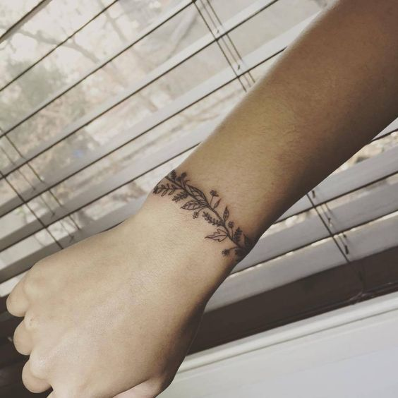 Flower arm band tattoo on the right wrist.