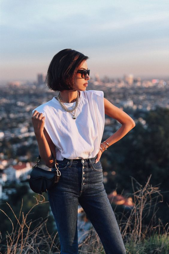 Casual outfit idea - white shoulder pad t shirt, blue high waisted jeans, Dior saddle bag, cool sunglasses, and a couple of necklaces to pull the look together #outfit #outfitidea #fashion #style #casualfashion #casual #whitetshirt #jeans #saddlebag
