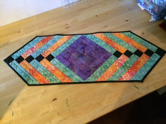 Modern Batik Table Runner Quilt - Orange, Green and Purple Quilted Table Topper, Table Covering by MyBitOfWonder on Etsy https://www.etsy.com/listing/230781447/modern-batik-table-runner-quilt-orange