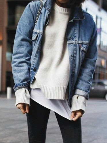 Denim jacket over winter white sweater and white tee with black jeans.