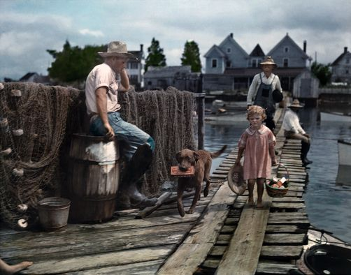 1930's color photography. Maryland - A child and her dog walk down the dock to meet the mail boat, Tylerton