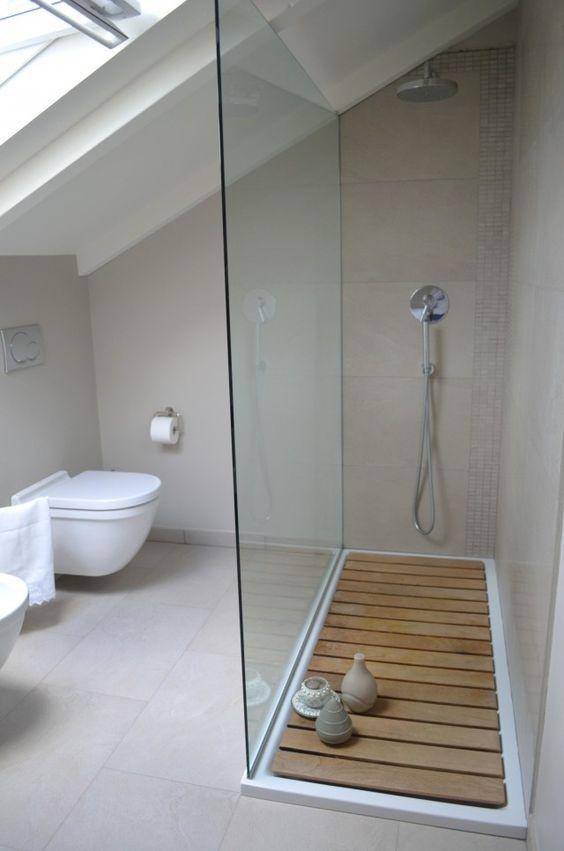 Glass shower wall, sunk-in floor even with rest of bathroom and walk-in, no door.