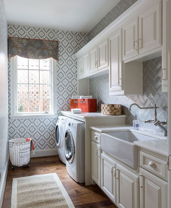 Off white laundry room cabinet painted in Sherwin Williams Alabaster and gray herringbone tile backsplash. Heather Scott Home & Design