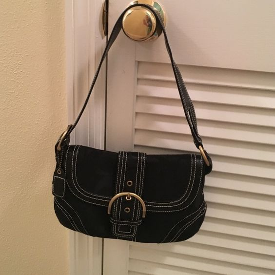 Black Coach shoulder bag NWOT black shoulder bag.  Gold buckles and hardware.  White stitching.  10 x 7 h . 9 strap drop.  Has snap closure pocket on back of purse.  Has zipper compartment inside.  Also has two pockets for cell phone and keys for easy finding. Coach Bags Shoulder Bags