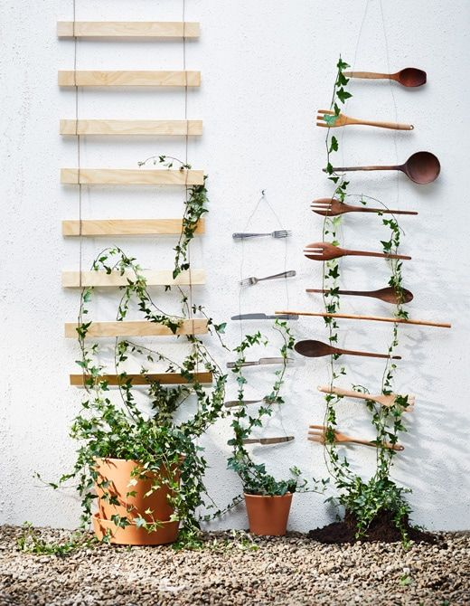 Several Wire Trellises Are Hung On A Wall And Display Plants In Small Glass Vessels Ikea Garden Diy Trellis Creative Gardening