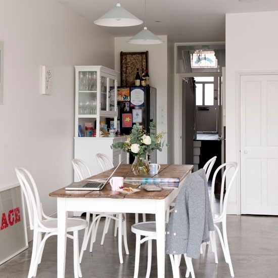 Painted second-hand furniture softens the sleek kitchen units in the corner, as well as the concrete flooring. The wooden top dining table adds a country-style element.