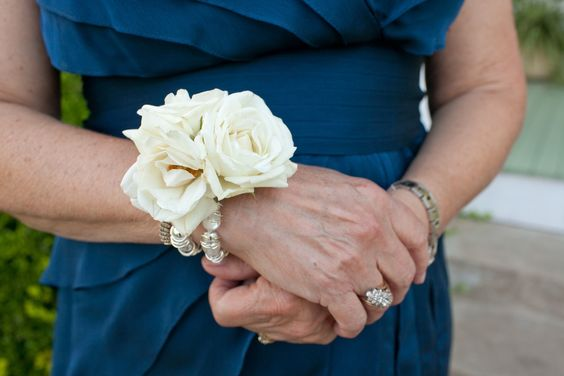 The mothers and grandmothers will have wrist corsages of ivory spray roses and gold seeded eucalyptus on a pearl beaded bracelet.