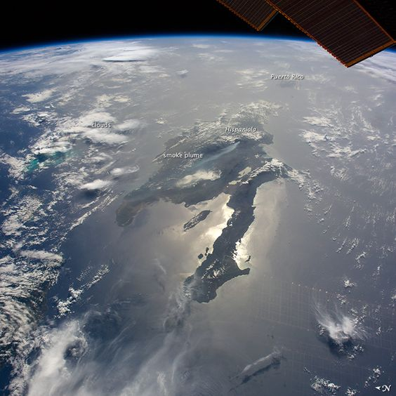 Looking east into a rising sun, the crew onboard the International Space Station (ISS) took this panoramic photo of the island of Hispaniola, with sunglint illuminating the long western peninsula of Haiti. Several thunderheads throw shadows towards the camera at image left.