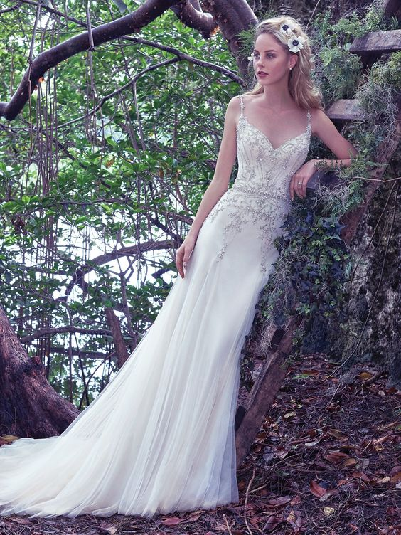 Maggie Sottero - ANDRAEA, Modern and romantic, this seemingly weightless slim A-line wedding dress is adorned with Swarovski crystals and glimmering beaded embellishments on soft tulle. Godet panels add soft volume and ethereal elegance to the skirt. Finished with sweetheart neckline and crystal buttons over zipper closure.