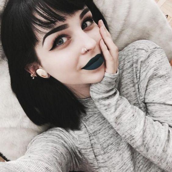 chica acostada con los labios negros: