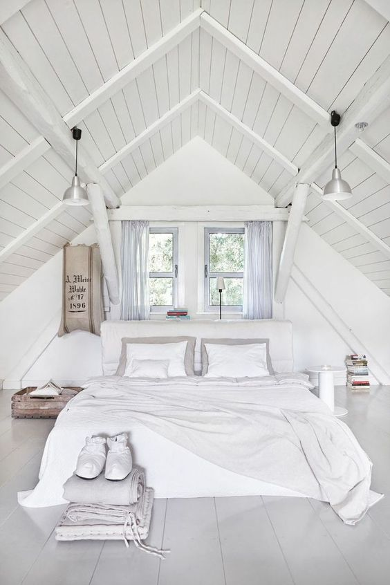 A pure white attic bedroom with an arched ceiling and two windows above the bed. Designed by http://jamkolektyw.com/ Loved by chicncheeky.com.au