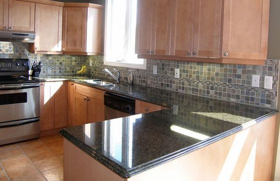 The tan colors in this kitchen are common in a lot of kitchens. With the black countertop, however, it gets a slightly different look that ties in well with the tiled backsplash.