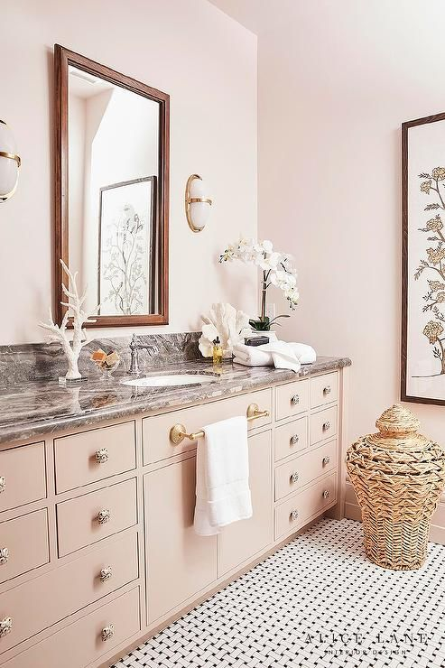 A Stained Wood Framed Mirror Hangs From A Pale Pink Wall Between White Glass And Brass Sconces Fitted Over A Light Tiger Oak Bathroom Interior Trendy Bathroom