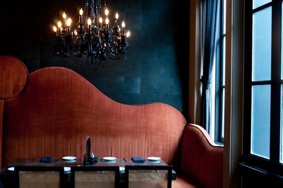 A monumental shaped banquette seat in a faded orange velvet set against a deep teal blue wall with chandelier