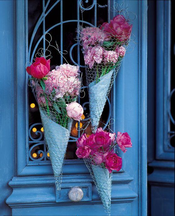 Des cornets en grillage remplis de papier de soie et fleurs fraîches et ornés de fil de fer