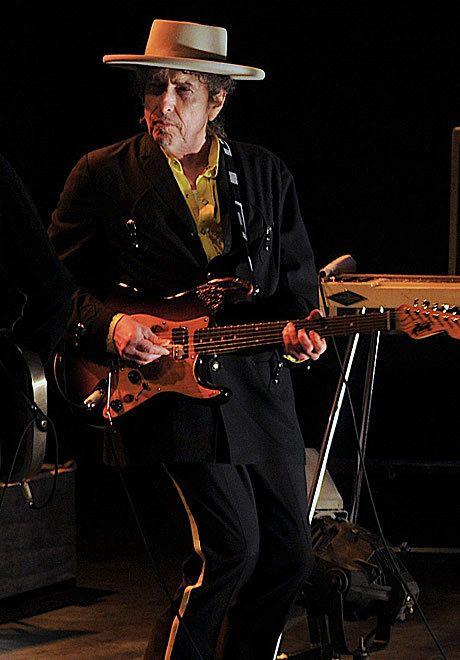 大きな帽子をかぶりギターを弾くボブ・ディラン