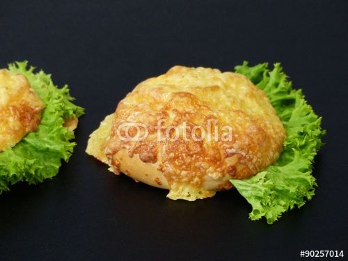 Käsebrötchen knusprig gebnbacken als Snack zum Frühstück mit frischem grünem Salatblatt