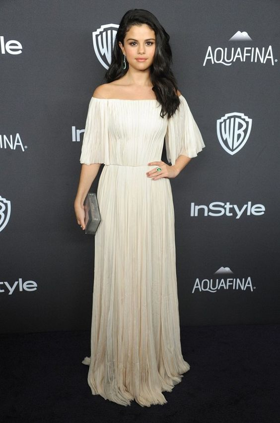 Selena Gomez wears a J. Mendel blush hand-pleated off-the-shoulder gown with Jacob & Co. jewelry and a metallic Rauwolf clutch.: