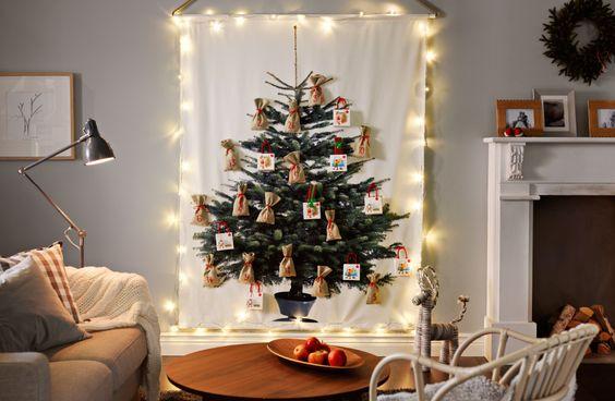 Sapin imprimé sur du tissu accroché au mur avec guirlande lumineuse et décorations de Noël accrochées.