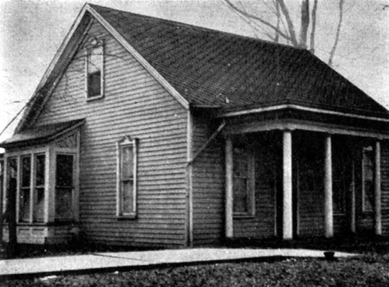 [image ALT: A photograph of a very small single‑story clapboarded wooden house, with a porch, supported by three columns, over the front door. It is the Edgar Lee Masters House in Petersburg, Illinois.]