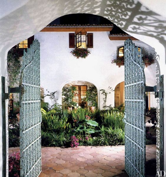 Original wrought-iron gates from the turn of the century open onto an enclosed patio paved with French terra-cotta tile and a pond stocked with koi at Steven Spielberg's Pacific Palisades, California, home.