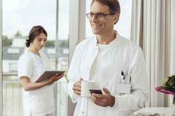 Doctor with coffee cup and smartphone, nurse working in background