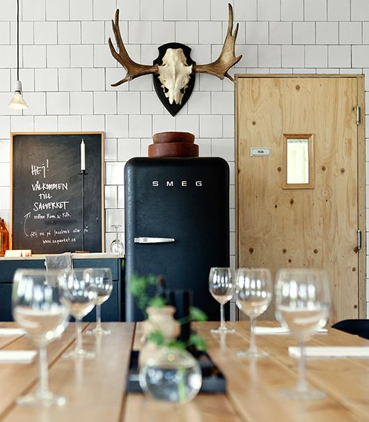 Love the black smeg fridge and other pieces against the white brick tiles and pale wood table.: