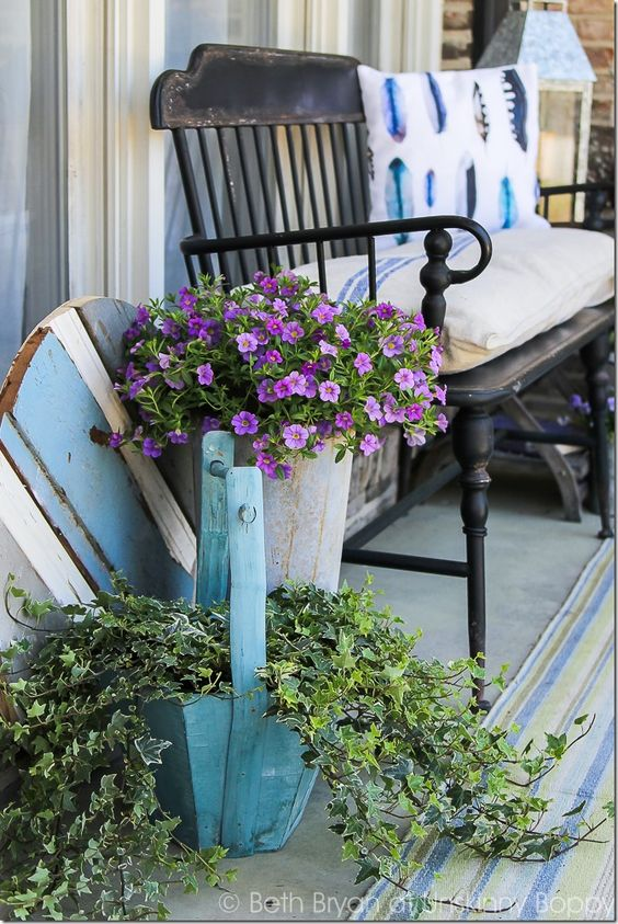 Black Metal Front Porch Bench With Watercolor Feather Pillow French Grain Sack Cushion And Flowers In A Buc Front Porch Decorating Spring Home Primitive Homes