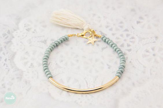 Ce magnifique bracelet dispose dun tube plaqué or et perles de rocaille de lumière gris mat (Mat). Très simple et mignon avec un gland et un charme