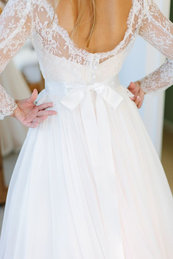 Low lace back with covered buttons and sash bow on the 'Fleur' Naomi Neoh blush wedding dress -  Image by Camilla Arnhold - Naomi Neoh Fleur blush wedding dress for a beautiful peach and online dating themed back garden wedding with unique gift ideas for bridesmaids