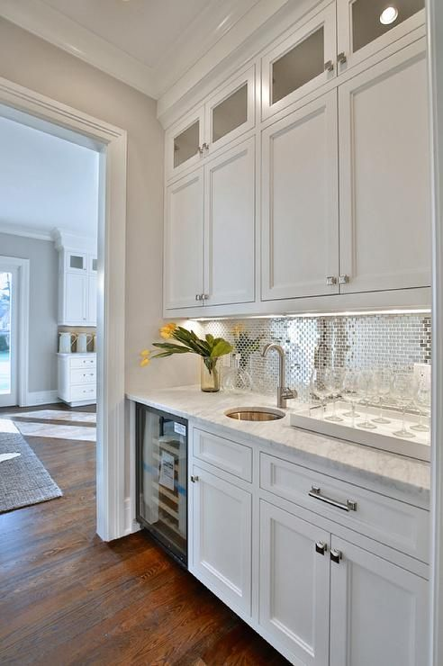 White and silver butler's pantry features white shaker cabinets paired with carrera marble countertops fitted with a round bar sink and a gooseneck faucet next to a glass front wine cooler and a stainless steel mini brick tile backsplash.