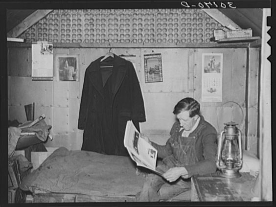 Gold miner reading in his shack. Two Bit Creek, South Dakota, 1937