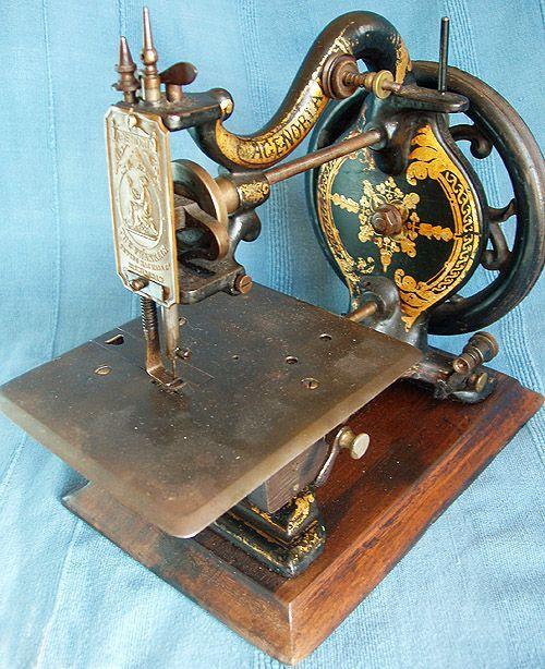 """This machine was probably produced c1870 and has the name Agenoria on the arm. The brass needlebar cover has a representation of the deity Agenoria - Goddess of Industry & Silence seated next to a prone Lion, there is also a Registered Design lozenge for 24th February 1869 (we think!) which appears centrally just beneath the machines name. Engraved on the cloth plate is the company trade mark which represents a bobbin with crossed needles with """"The Franklin Co."""" round it."""