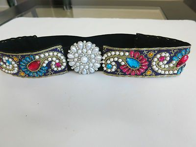 Embroidered, flower jeweled pearl buckle stretch belt.       Faux White Pearl, Peacock Blue and Pink oval and round shape stone work enhances it's elegance.       Combination of Pink,Blue And White colors looks amazing with mini Yellow stones work at the center.      The base is a Violet brocade shiny look fabric with golden print.      Silver tone flower jeweled pearl buckle in front.