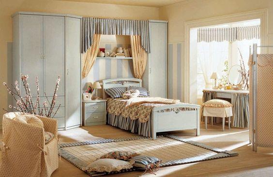 Dormitorio individual. Este es una otra habitación individual que se aparece a la otra. Está la cama con tres almohadas y una manta, a la izquierda está el armario y sobre la cama una estantería. Al lado de la cama está también un escritorio con una silla. En el centro del dormitorio hay un alfombra con muchas almohadas y un sillón.