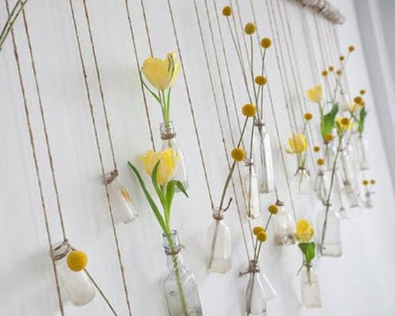 Tie twine around small glass bottles holding real or fake flowers, then tie them off on a large hanging rod/stick. Make it your own!