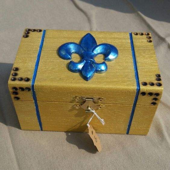 Wood box in metallic gold and blue with fluer de lis medallion and wood burned details.