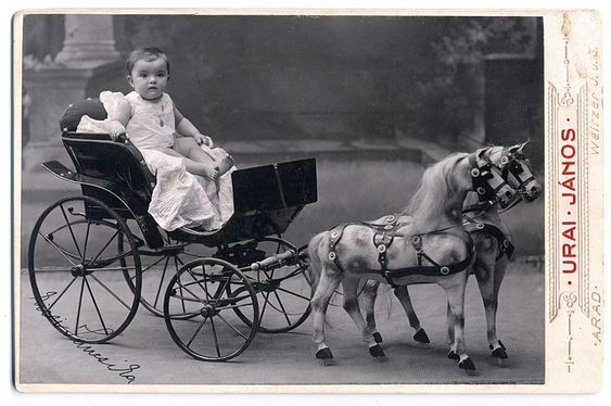 little child riding an amazing carriage with toy horses, 1910: