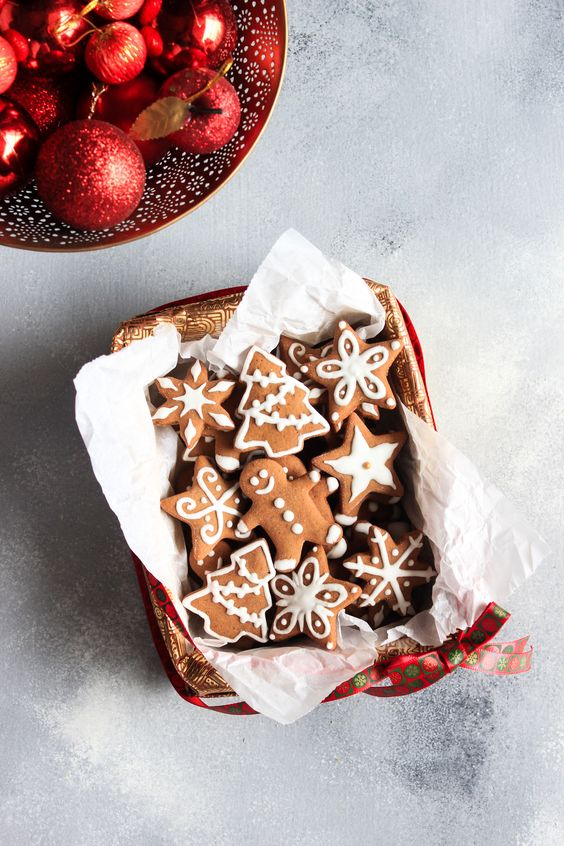 Pretty tiny Gingerbread Men and Gingerbread Cookies styled simply in a gift box with a ribbon and Christmas Baubles! Christmas Food Photography. Gingerbread Photography. Gingerbread Recipe. #foodphotography #christmas #cookies #gingerbread #royalicing #icing #recipe #christmascandy #holidays #baking
